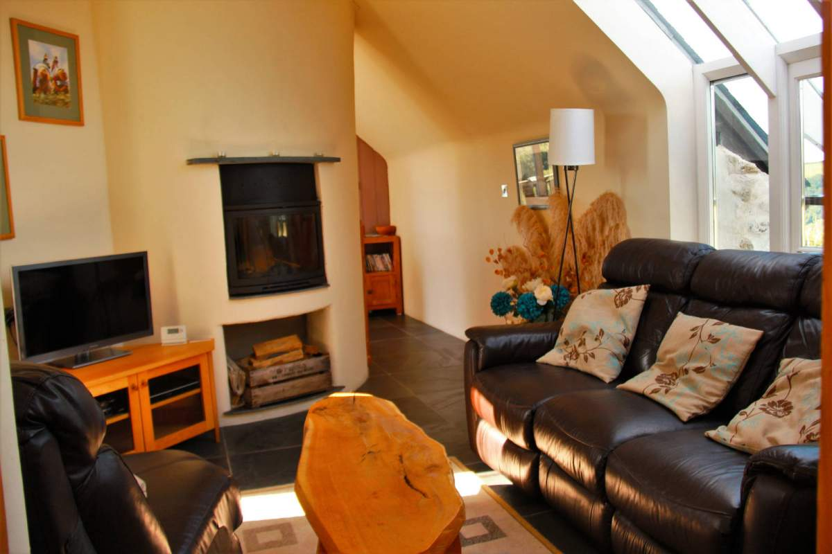 Snug upstairs lounge with log burning stove and views across the Gwaun Valley and Dinas Mountain